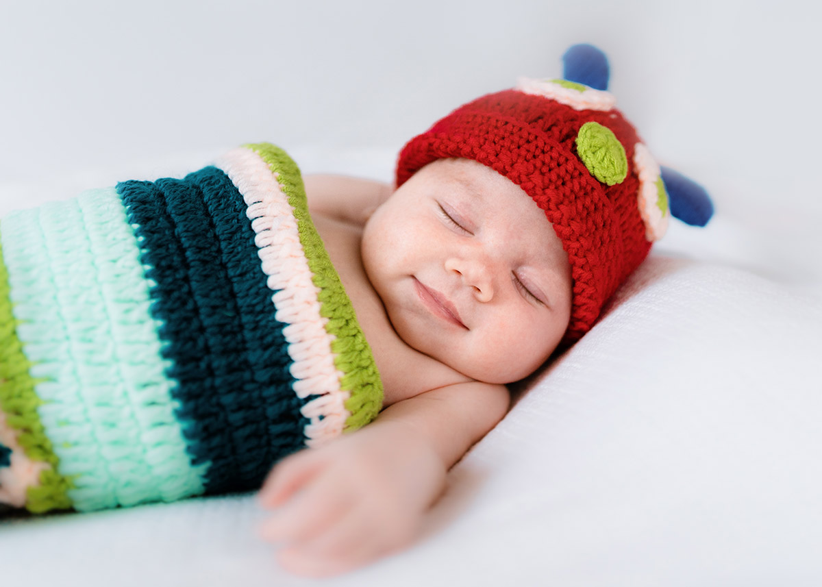 Newborn baby wearing caterpillar outfit smiling - Newborn Photographer - Perfect Story Photography