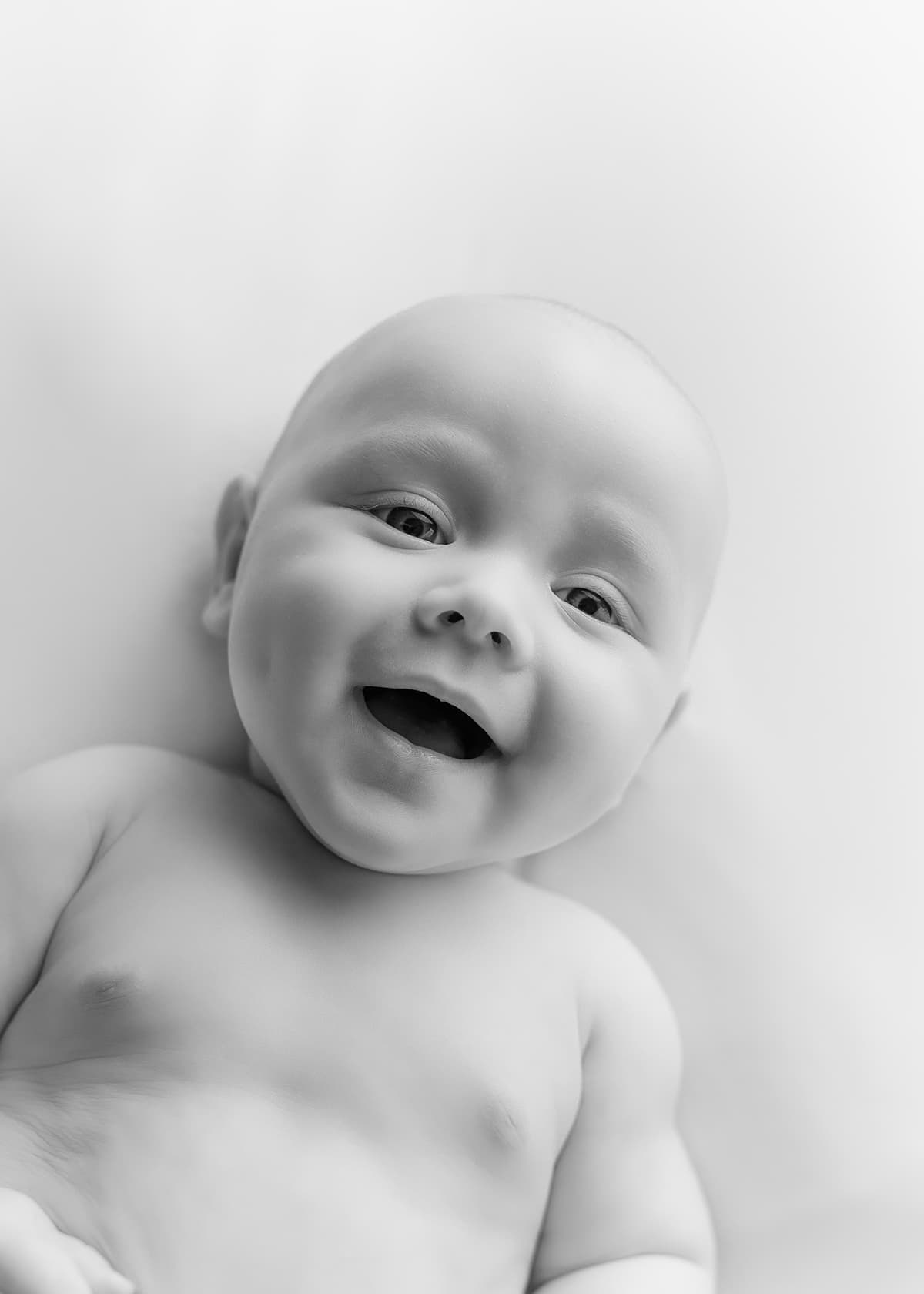 Newborn Baby boy smiling and laughing at camera in black and white photo - Newborn Photographer - Perfect Story Photography