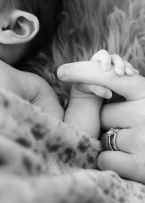 Newborn Baby holding mothers finger in black and white photo - Newborn Photographer - Perfect Story Photography
