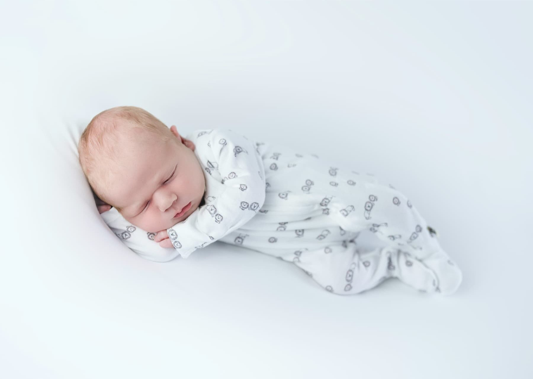 Newborn baby lying down in sleepsuit - Newborn Photographer - Perfect Story Photography